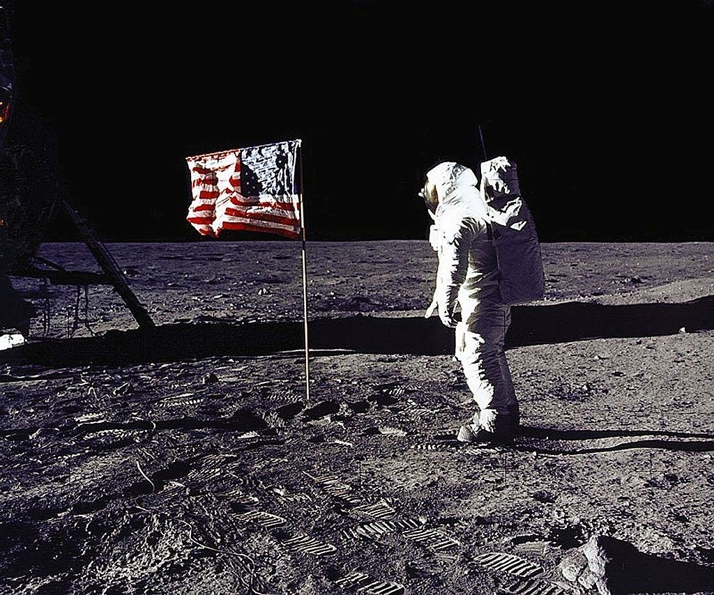 Buzz Aldrin standing next to the American flag on the moon