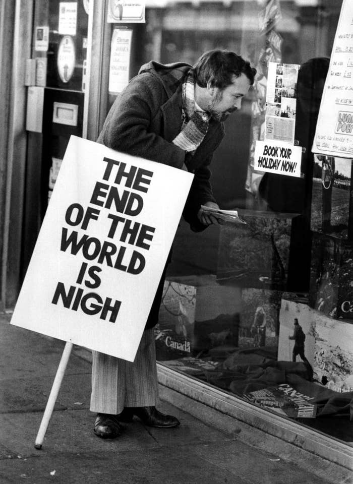 """A man holding a sign reading """"THE END IS NIGH"""" looks at an advertisement for vacations"""