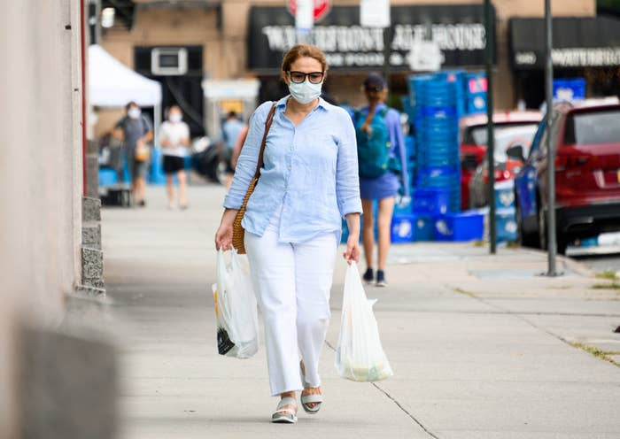 A person wearing a face mask walking down a sidewalk as they carry bags of groceries