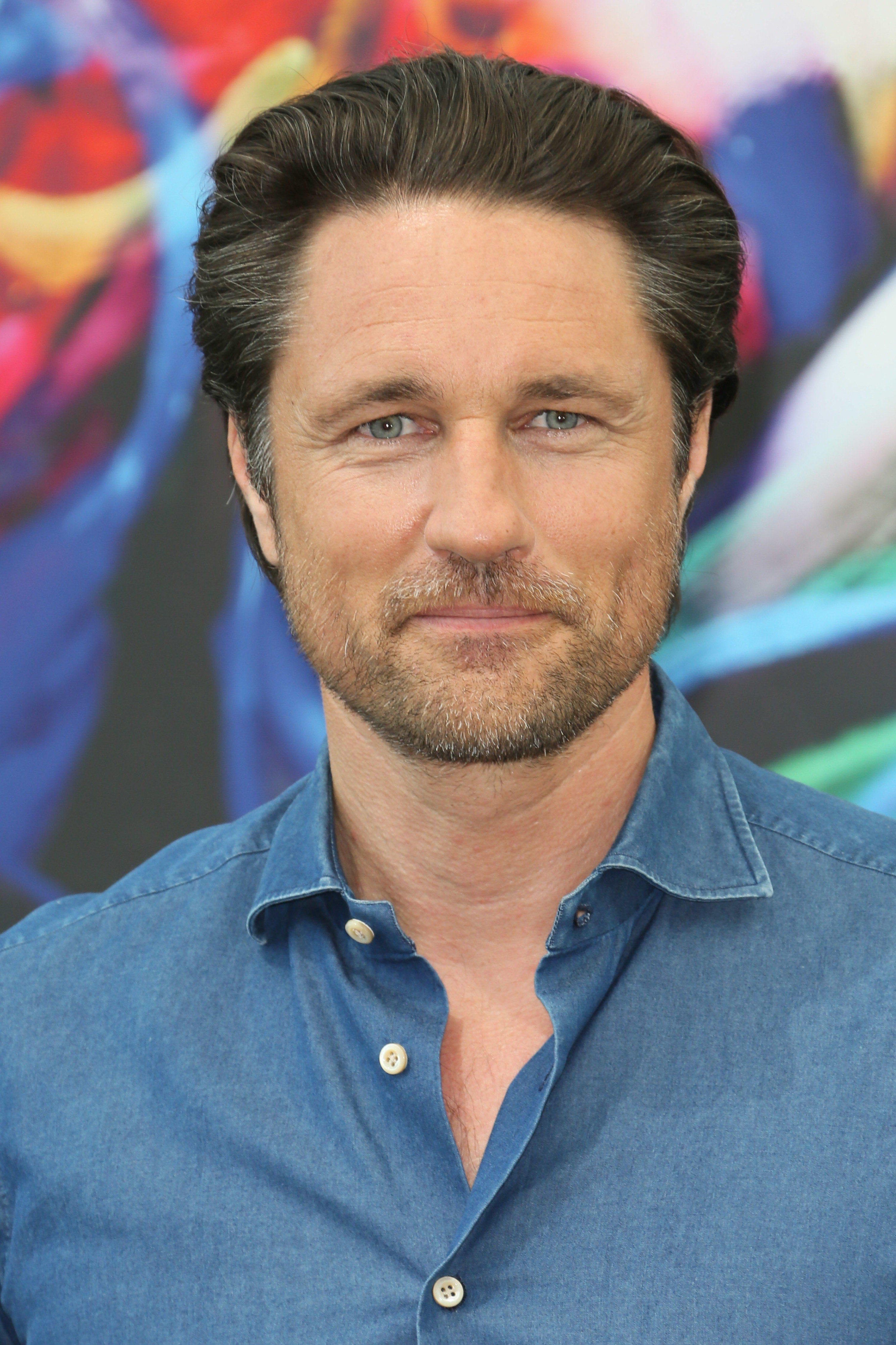 Martin Henderson siles for camera in blue button-up