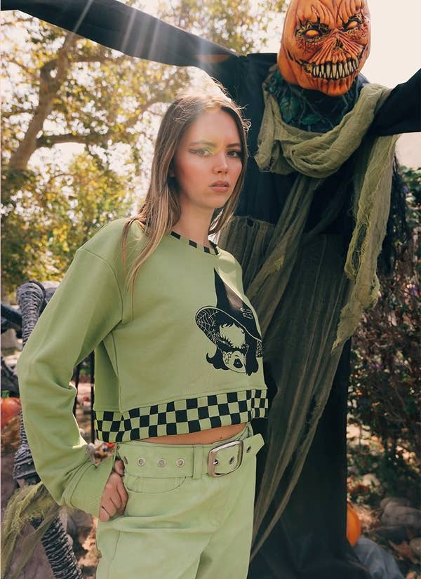a model wearing the cropped hoodie next to halloween decorations