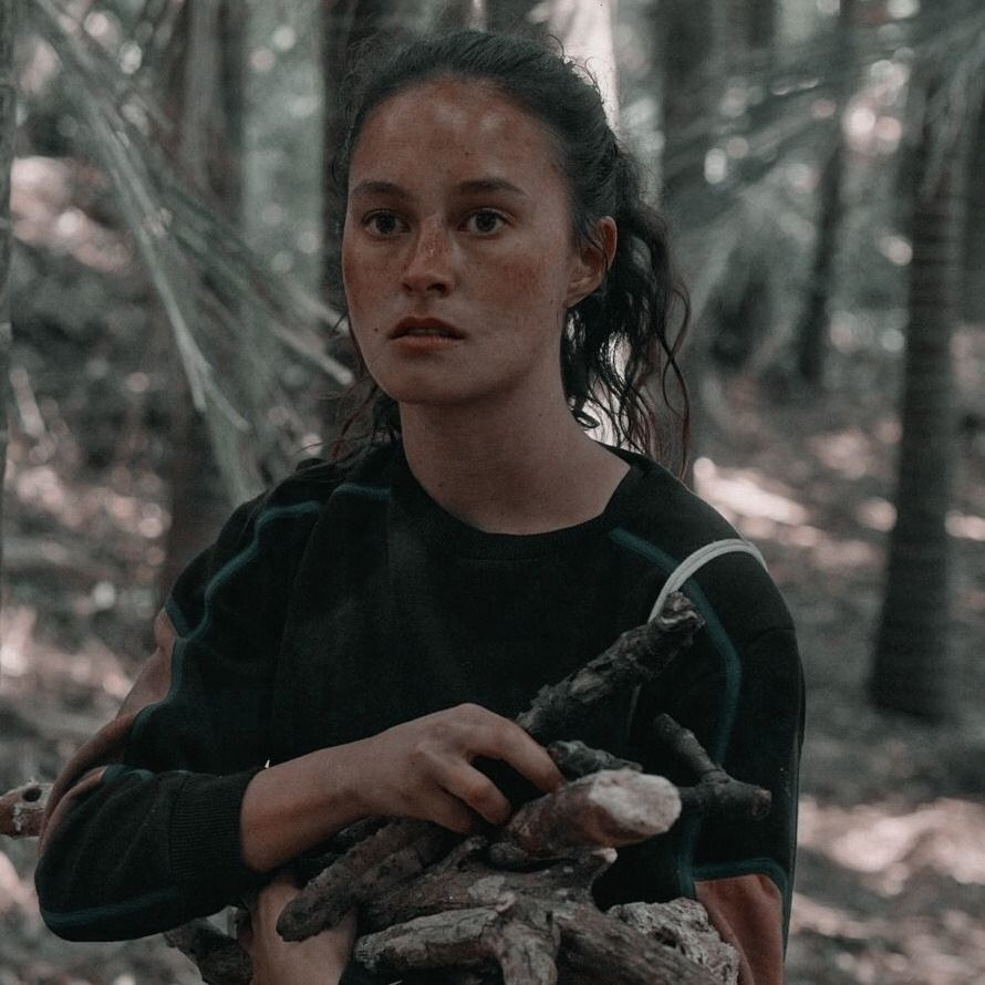 Erana James carrying wood during a scene in The Wilds