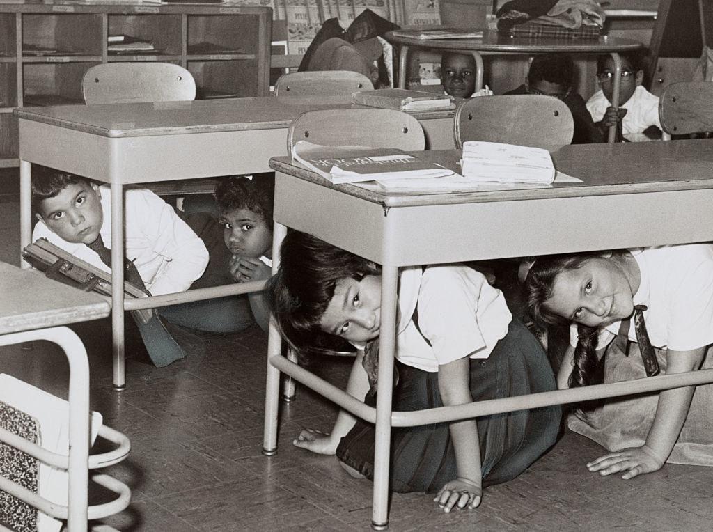 Children hide under school desks during a nuclear attack drill