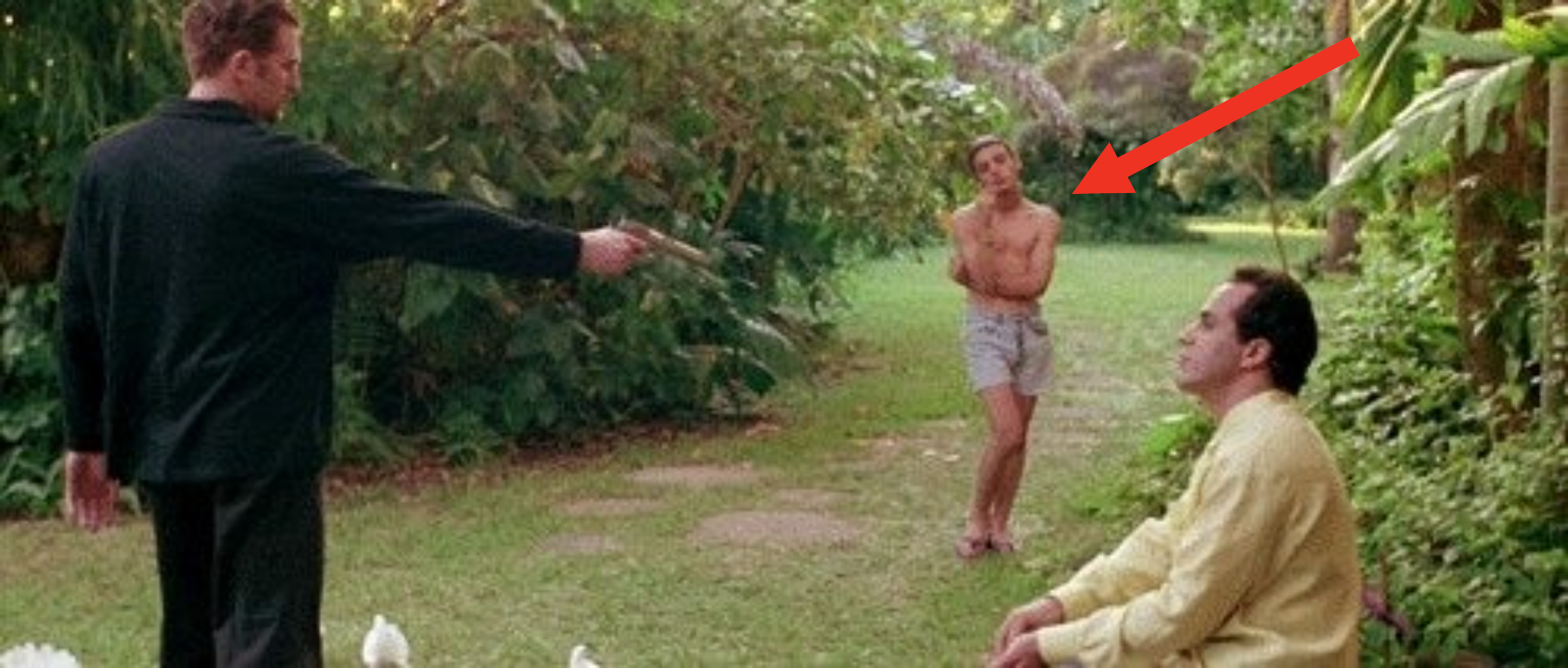 """Still from """"Illtown"""" with Oscar in the background shirtless and in jorts, Michael and Tony are on the left and right of him in the foreground, respectively"""