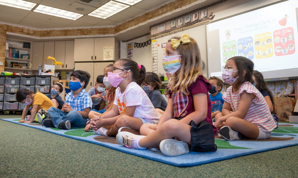 A group of small children wear their face masks and sit cross-legged in a classroom