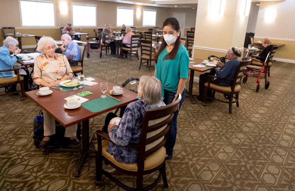 An employee speaking to two residents at an assisted care facility