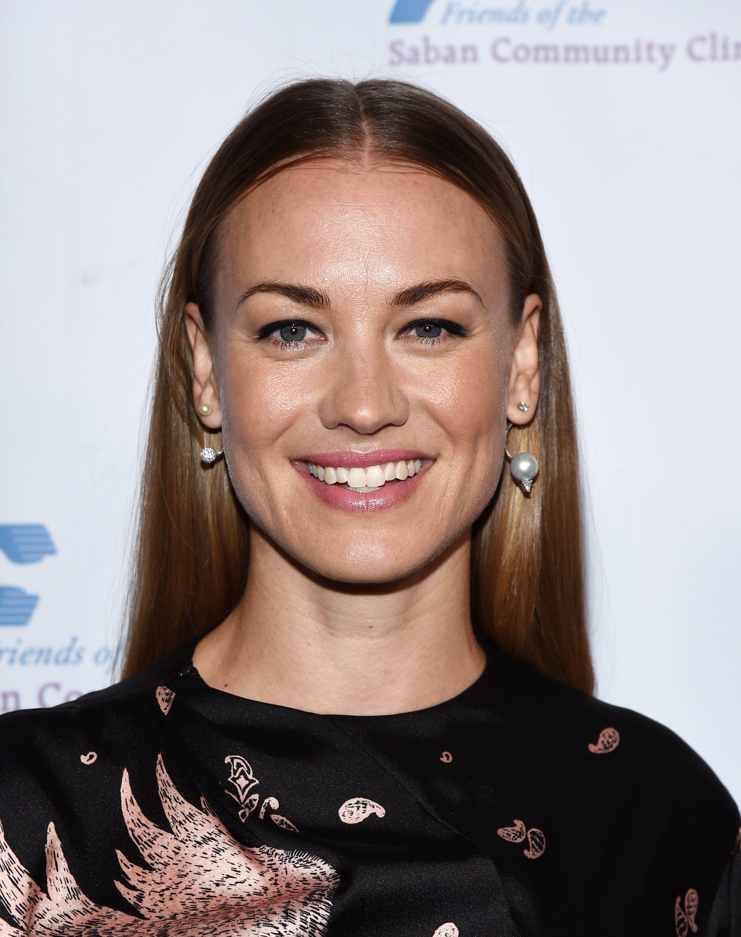 Yvonne Strahovski smiles in printed black dress and pearl-drop earrings