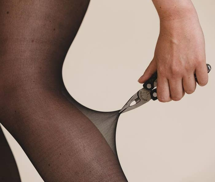 A person pulling at the leggings with pliers