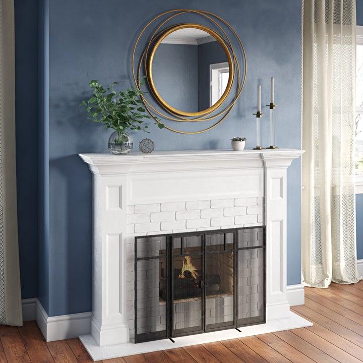Gold circular mirror above fireplace