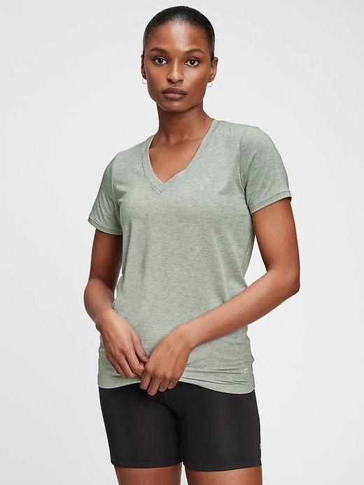 model in light green V-neck tee and black bike shorts