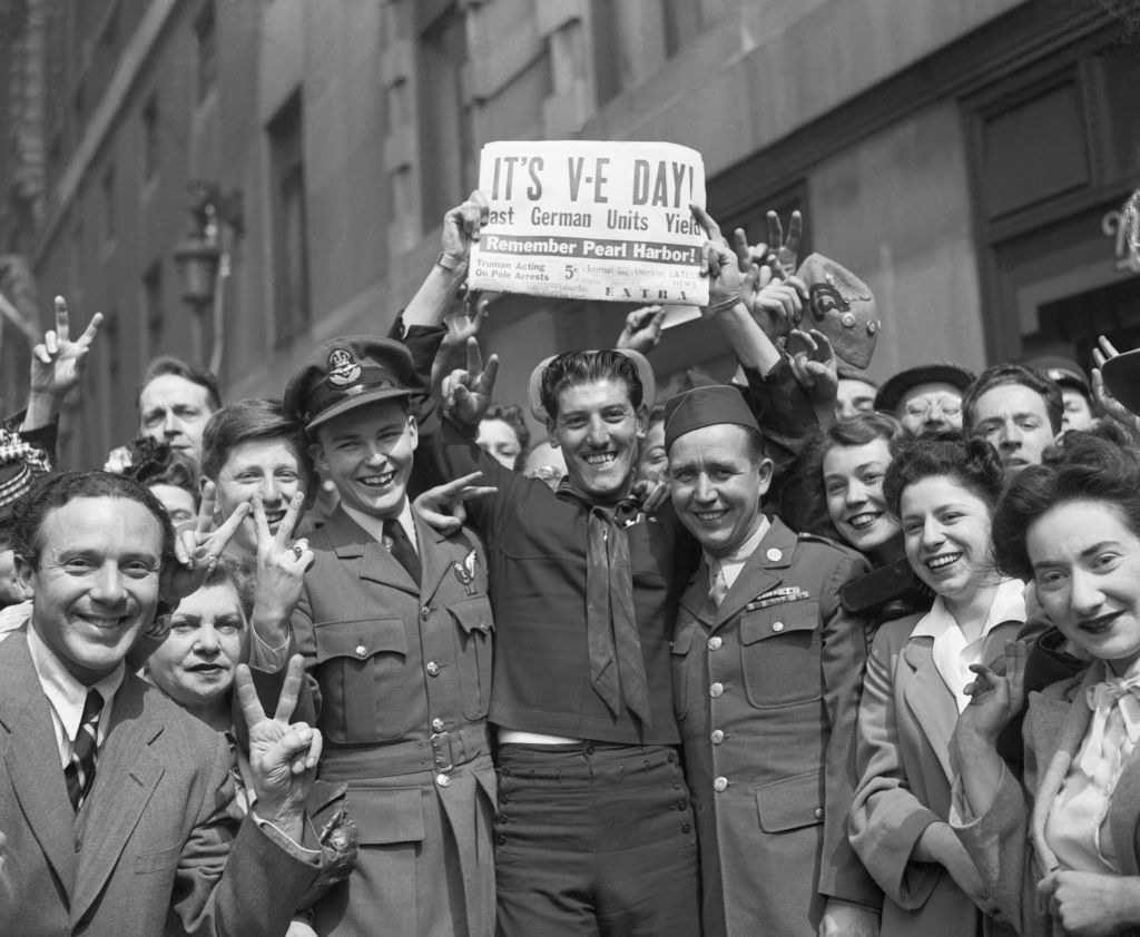 A soldier holds up a newspaper announcing Victory in Europe