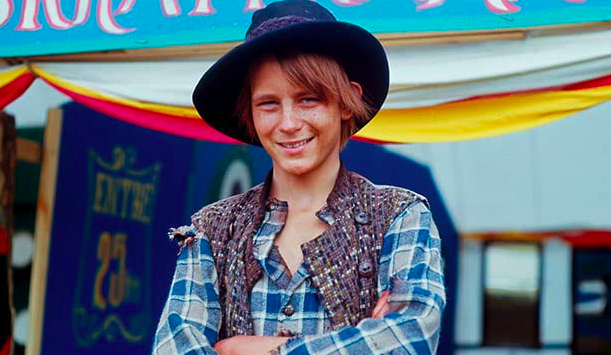 "Photo of Stellan in ""Bombi Bitt och jag,"" he wears a fedora-like cap, flannel button-down and multicolored vest"