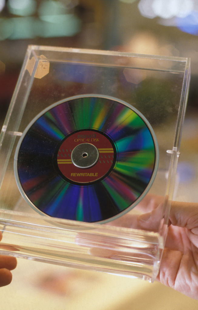 A rewritable CD in a clear plastic case being held in a person's hands
