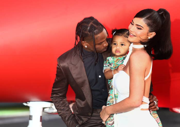 Travis Scott with his arm around Kylie as she holds their daughter Stormi