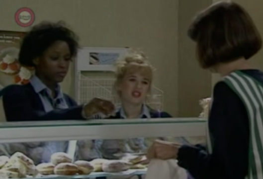 """A still of Sharon in """"2Point4 Children,"""" she's next to a blonde actress and faces Belinda Porter, whose back is to the camera, they're in a bakery"""