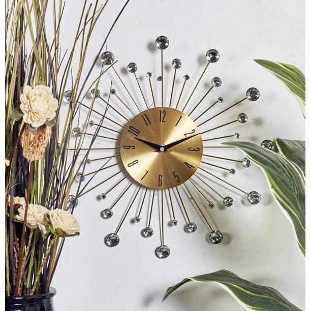 the sunburst clock in gold