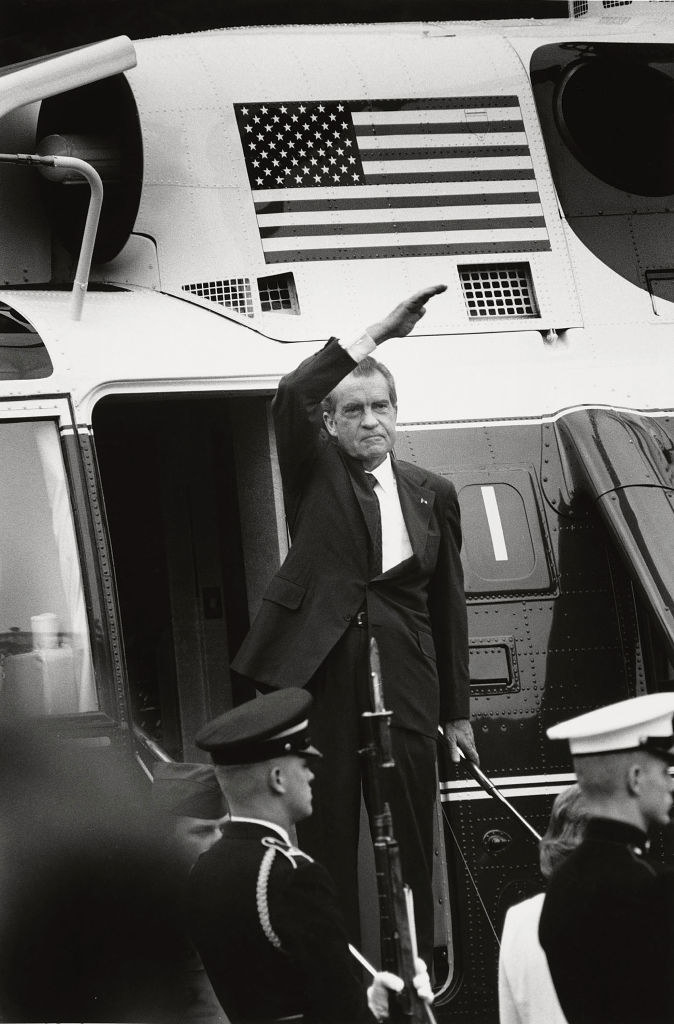 Nixon waves as he leaves the White House in a helicopter