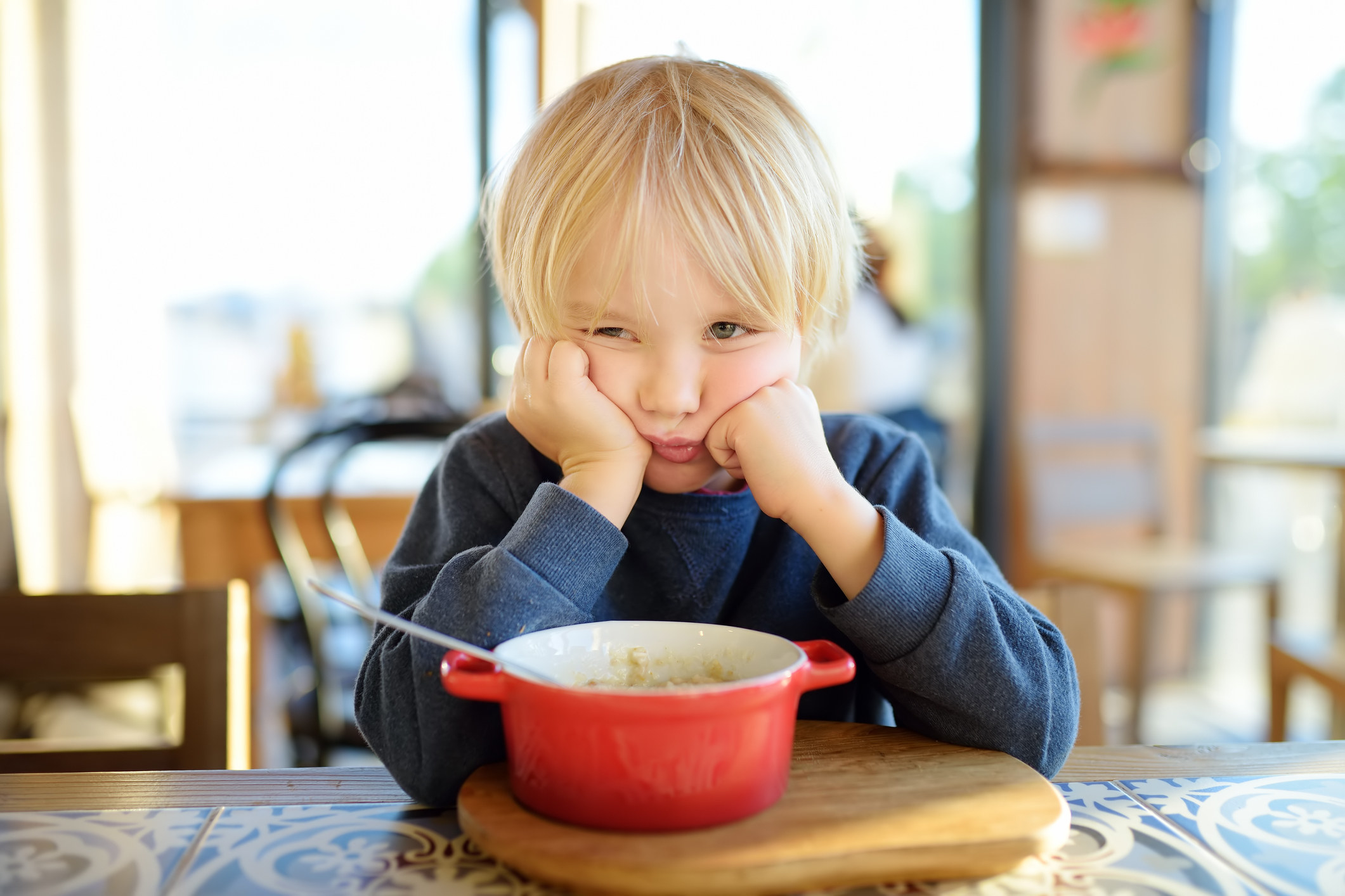 A kid sitting at the table but doesn't want to eat