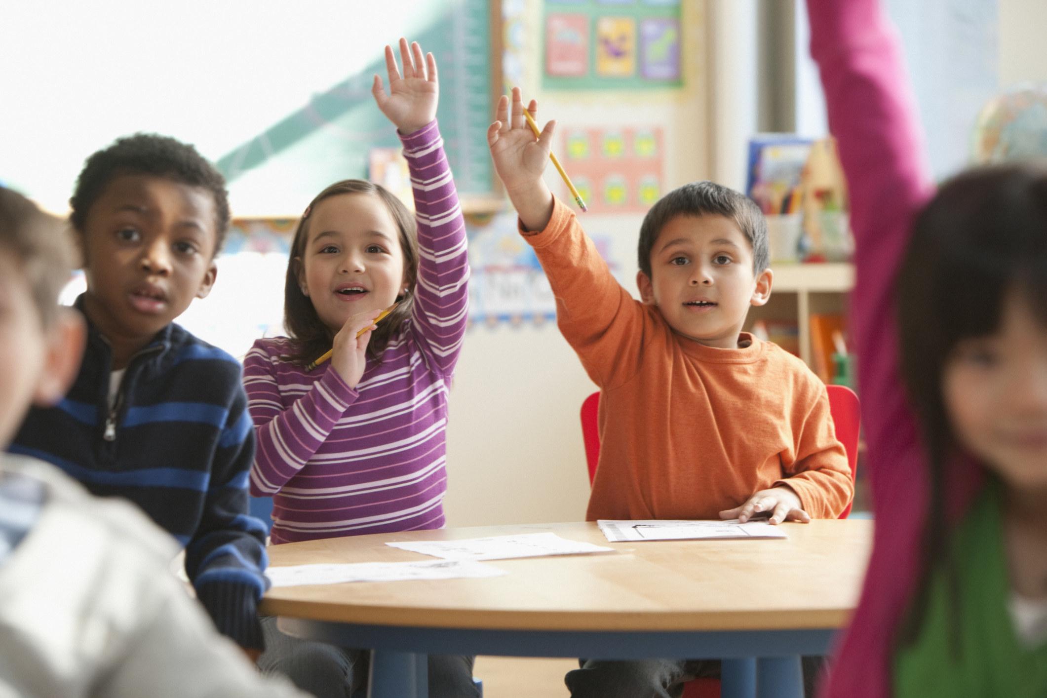Kids in a classroom raising their hands
