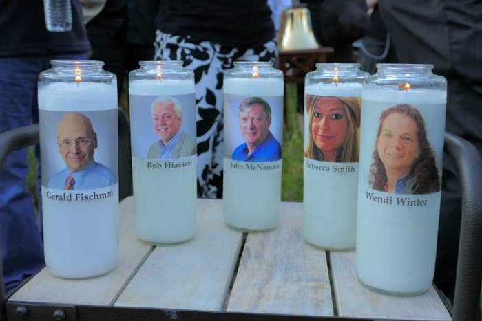 Five faces are printed onto labels of white candles