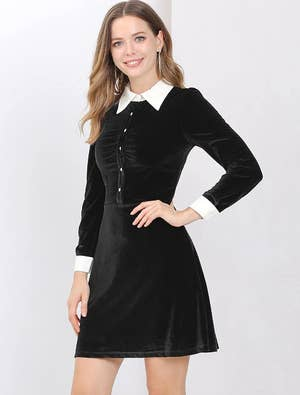a model wearing the black collared velvet dress
