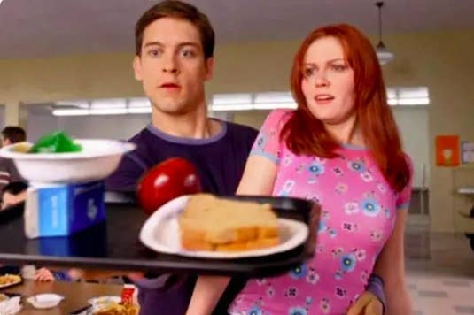 Peter Parker balances a lunch tray in one hand and Mary Jane in the other