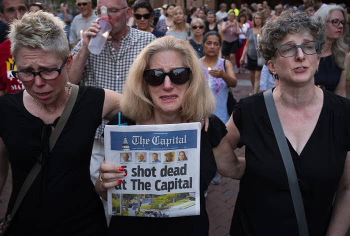 """A woman weeping behind sunglasses stands between two other women in a crowd and carries a newspaper that reads """"5 shot dead at the Capital"""""""