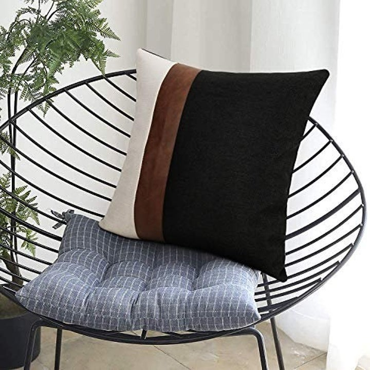 Mixed media brown, black, and white pillow on a chair