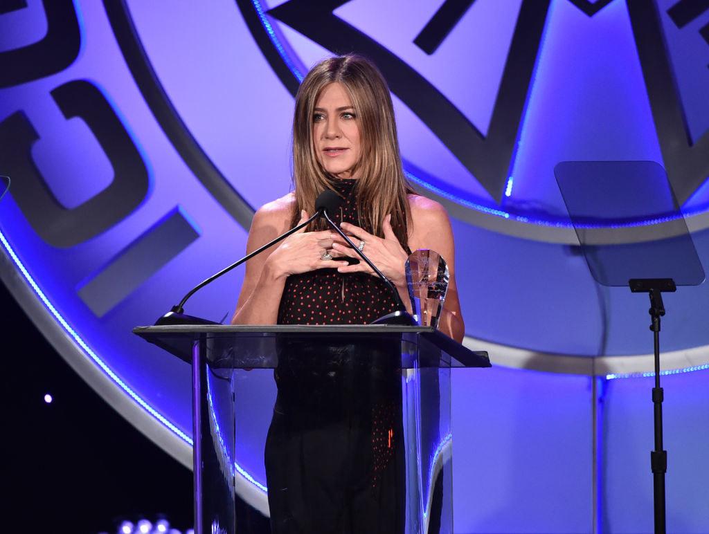 Jennifer speaking at a podium during an awards show