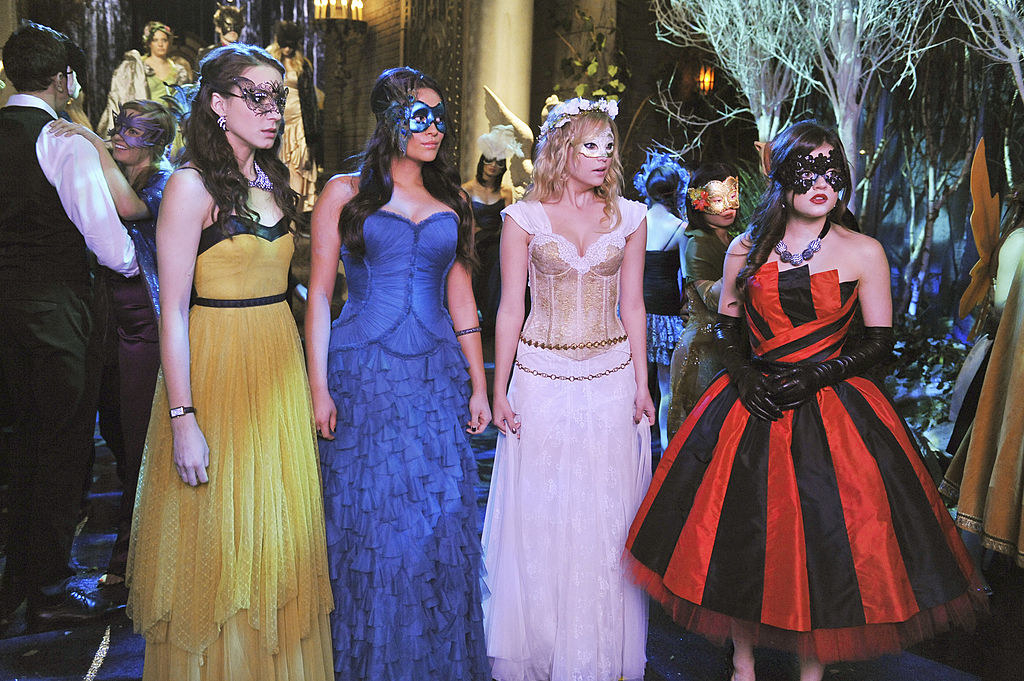 All four girls dressed in dramatic ball gowns for a masquerade