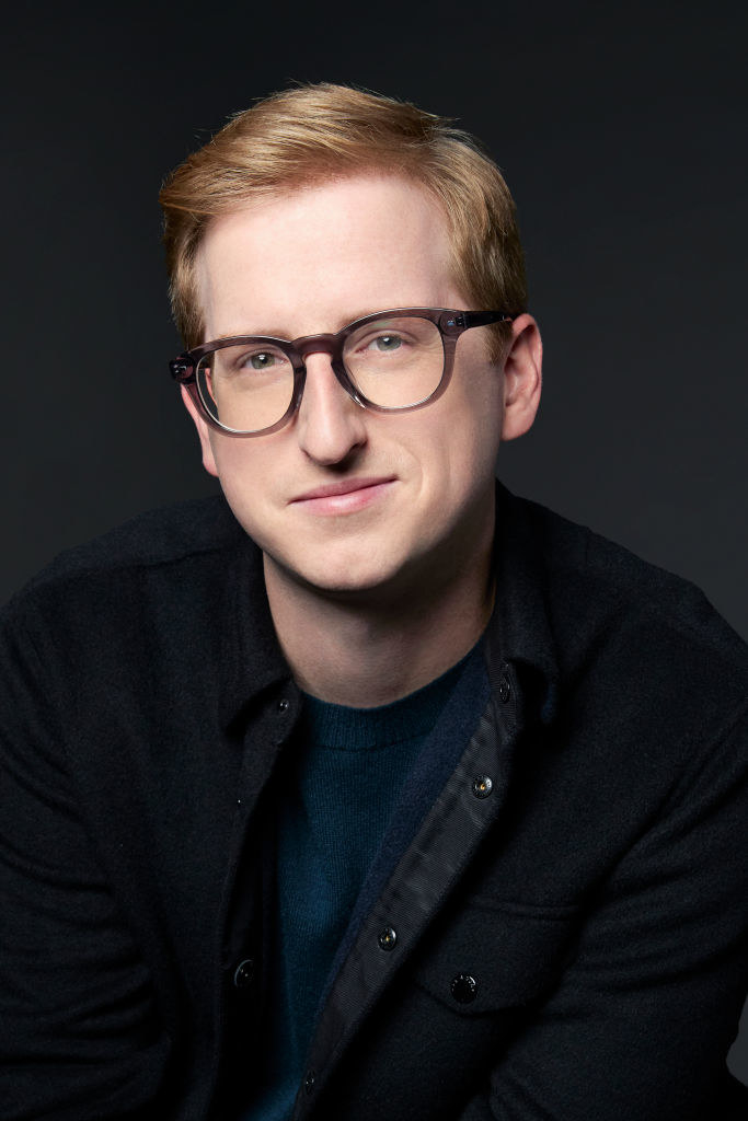 James in a professional photo wearing a dark-colored jacket and eyeglasses