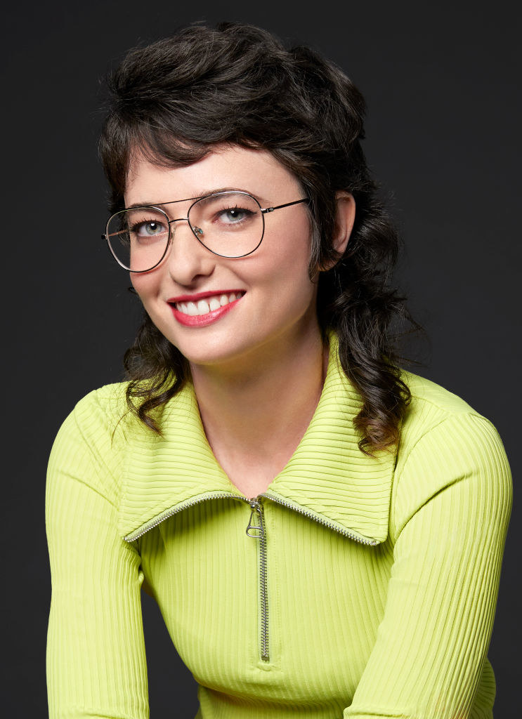 Sarah wearing a neon-colored sweater shirt and eyeglasses