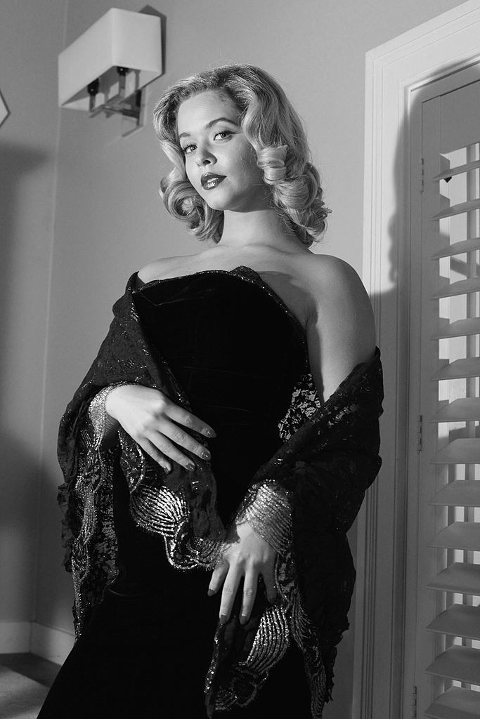 Ali dressed in a film noir style gown with her hair pinned up
