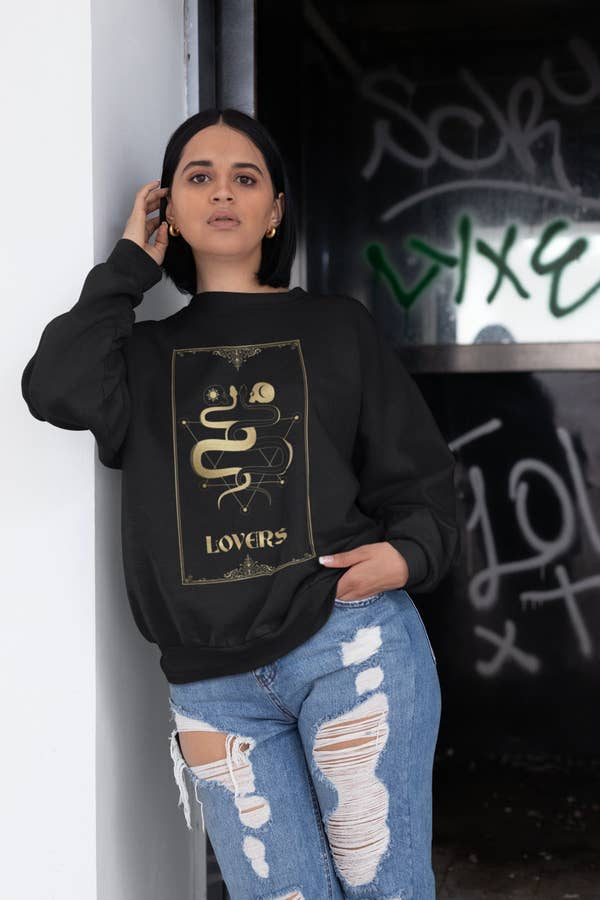 a model wearing the lovers sweatshirt with distressed jeans