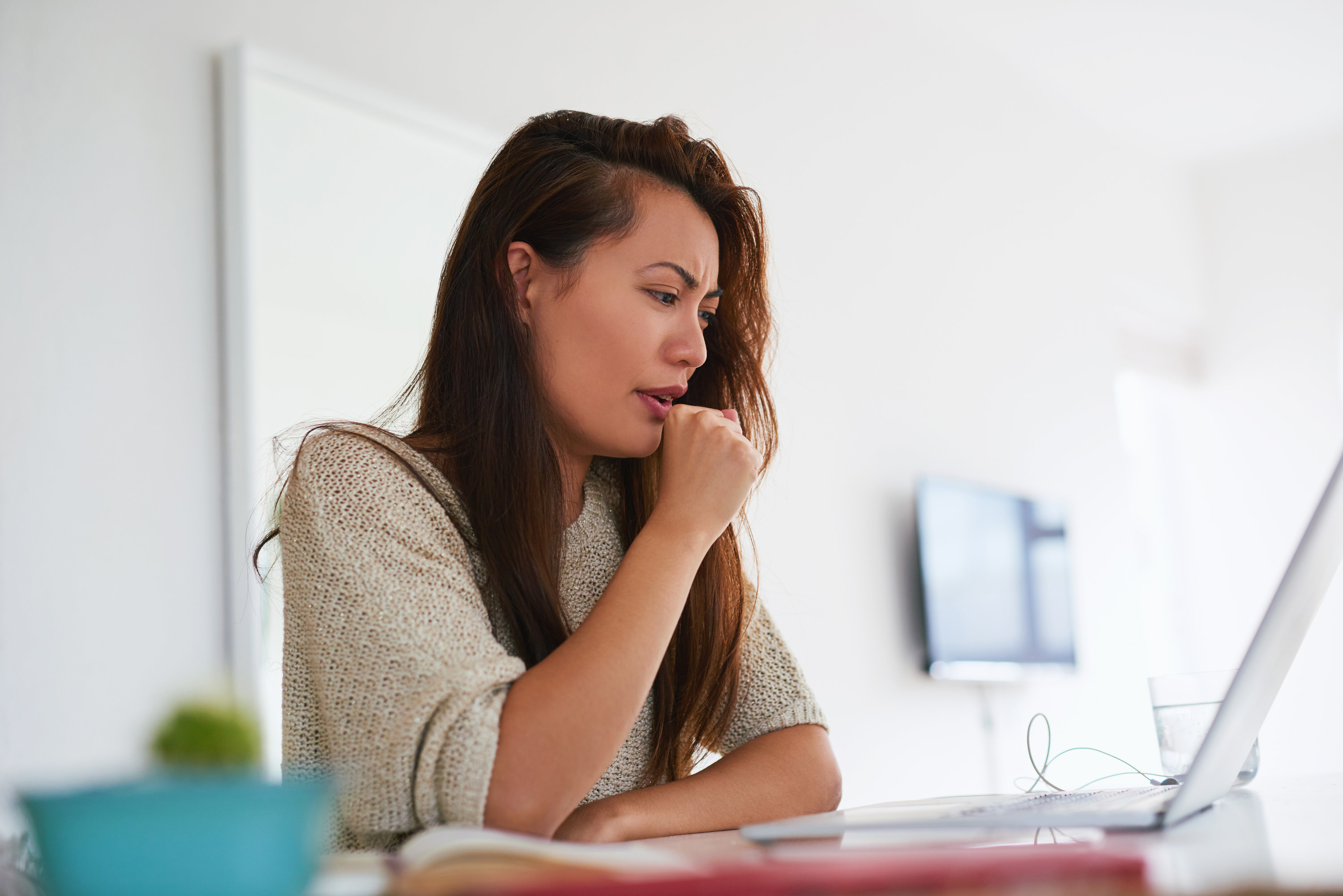 Person coughing and choking in front of a laptop