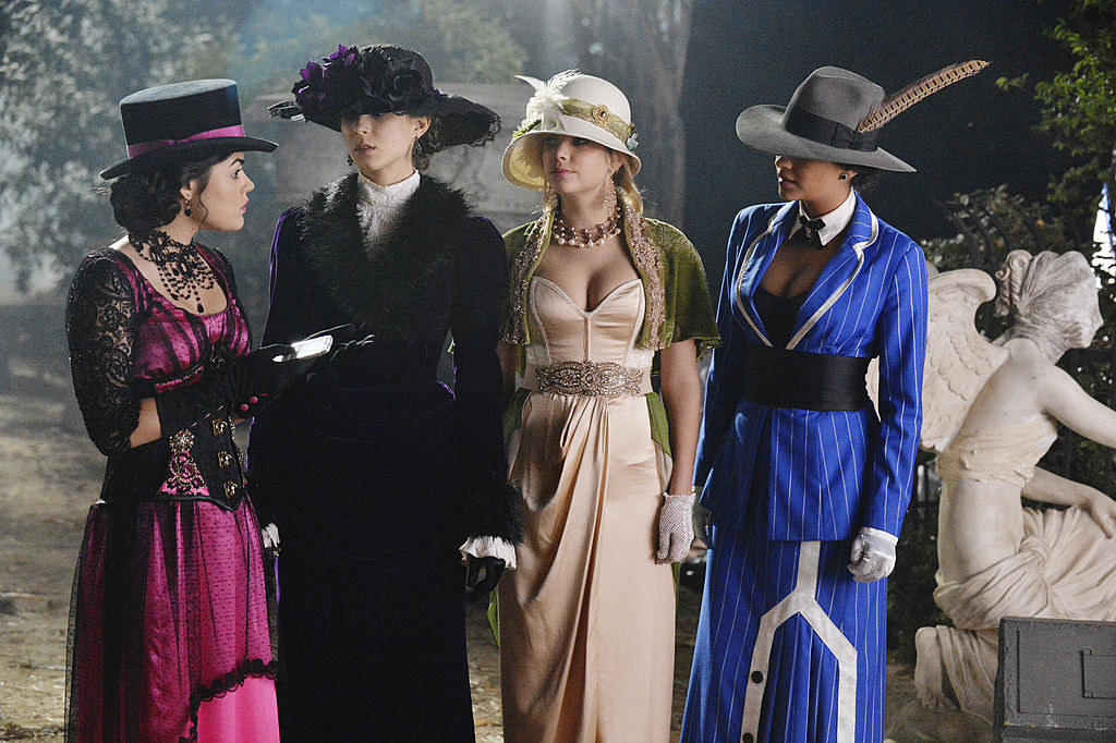 all four girls wearing Edwardian-style ball gowns with intricate details