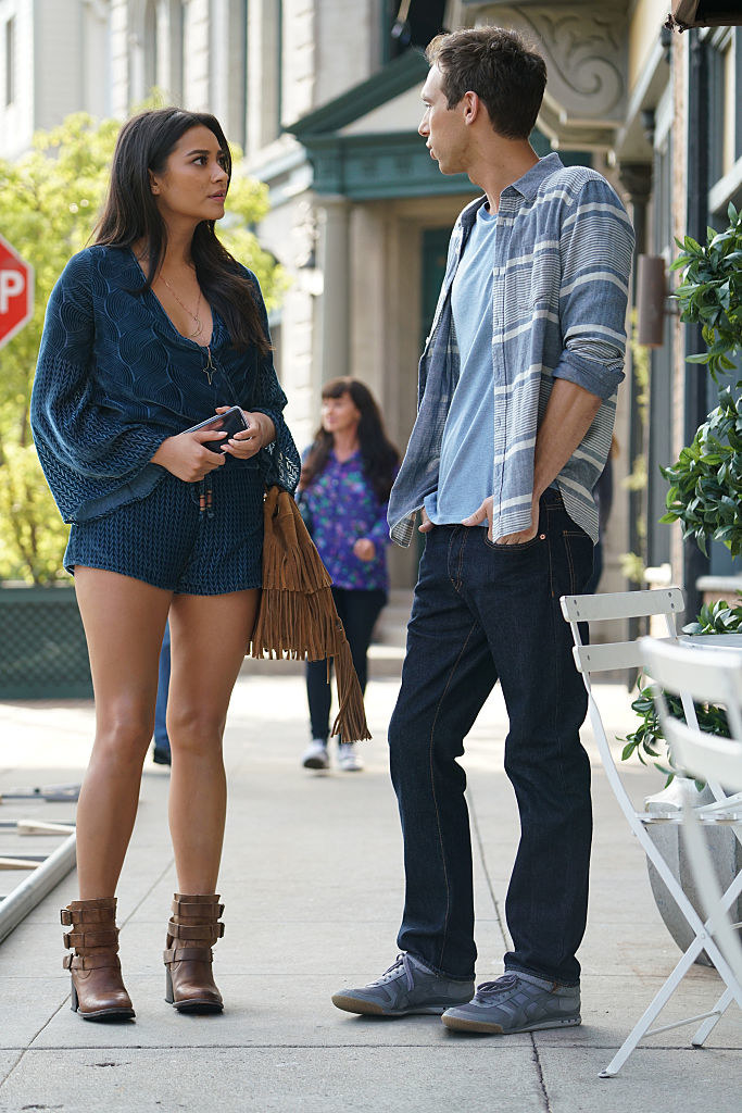 Emily wearing a blue romper and brown boots