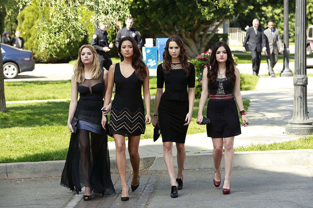 All four girls wearing black, sexy dresses to a funeral