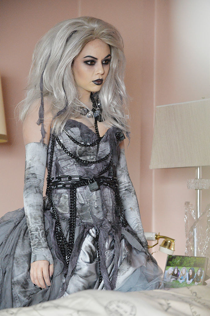 Monda dressed in ghostly makeup and a white wig with gray, chained dress