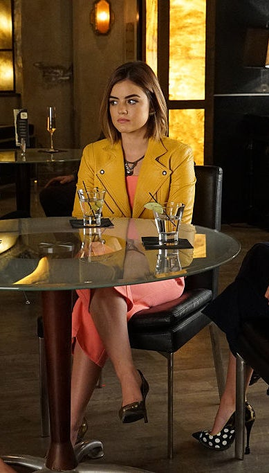 Aria wearing a yellow leather jacket and brown heels