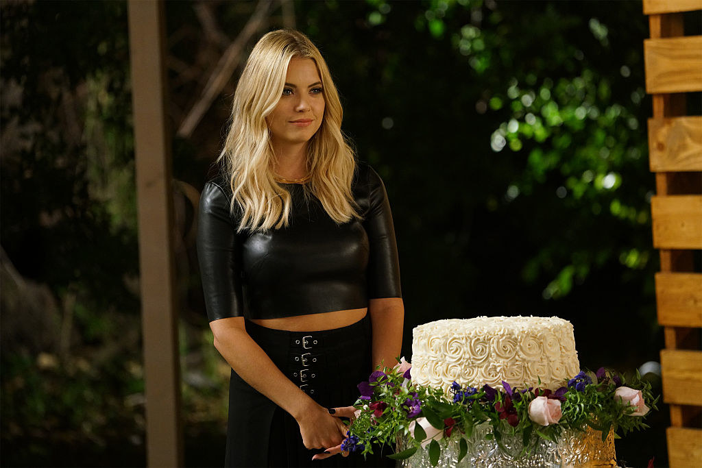 Hanna wearing a black crop top and black belted skirt