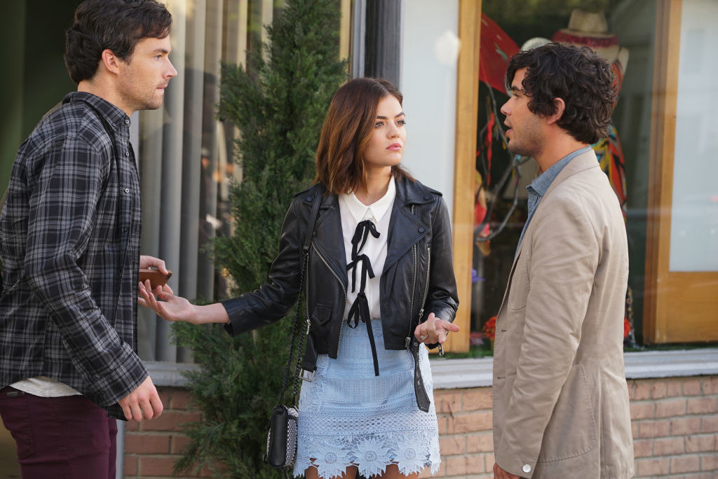 Aria wearing a light blue skirt with a black leather jacket and white blouse