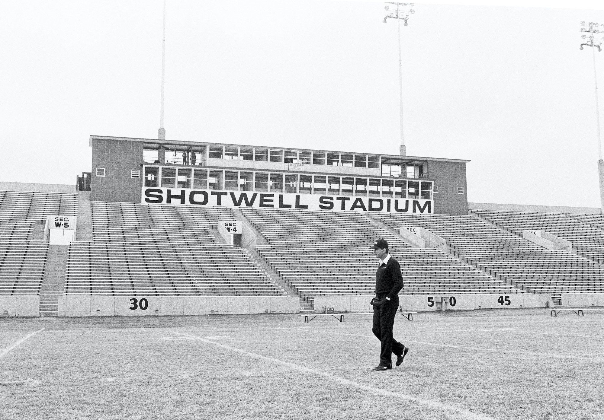 """Man wearing a cap walks on the field in an empty stadium with sign """"Shotwell Stadium"""" in background"""