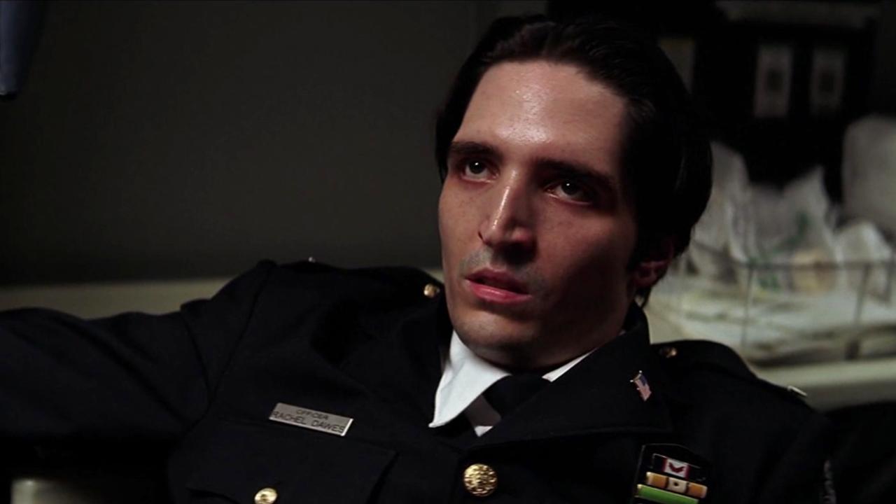 "David in a police uniform looks off-camera in ""The Dark Knight"""