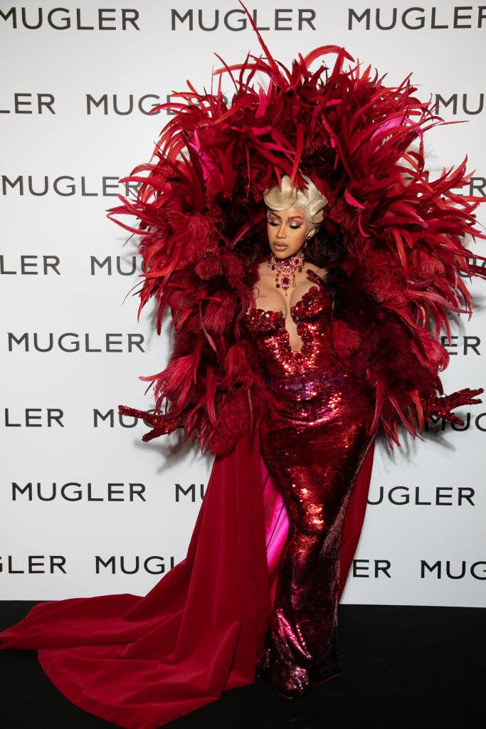 Cardi posing with her hands outstretched in a sequined strapless gown with matching feathered coat with a hood that hovers over her head