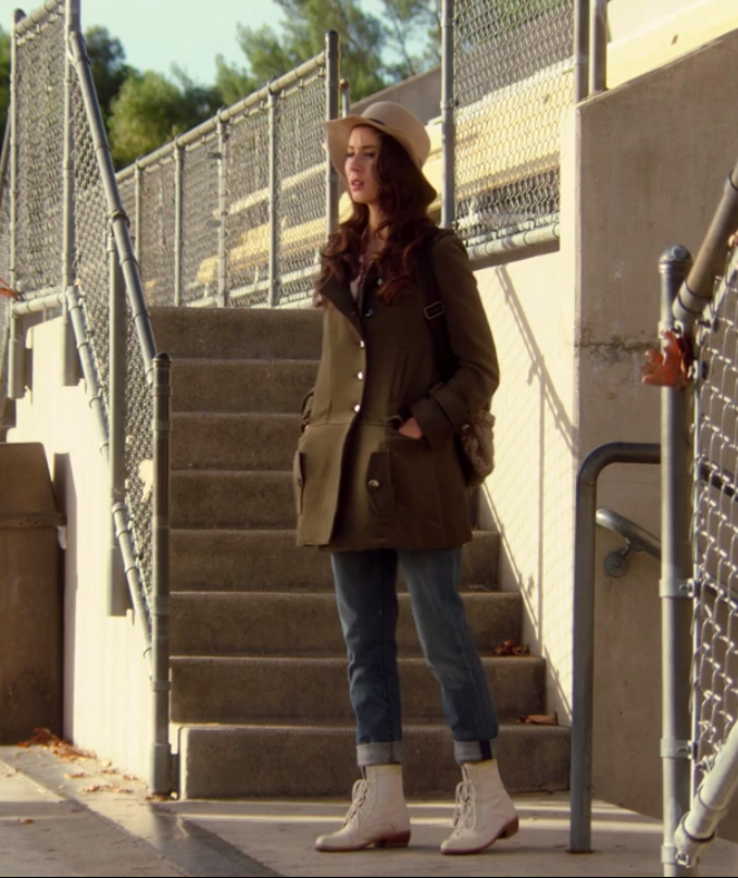 Spencer wearing white, laced boots, jeans, and a trench coat