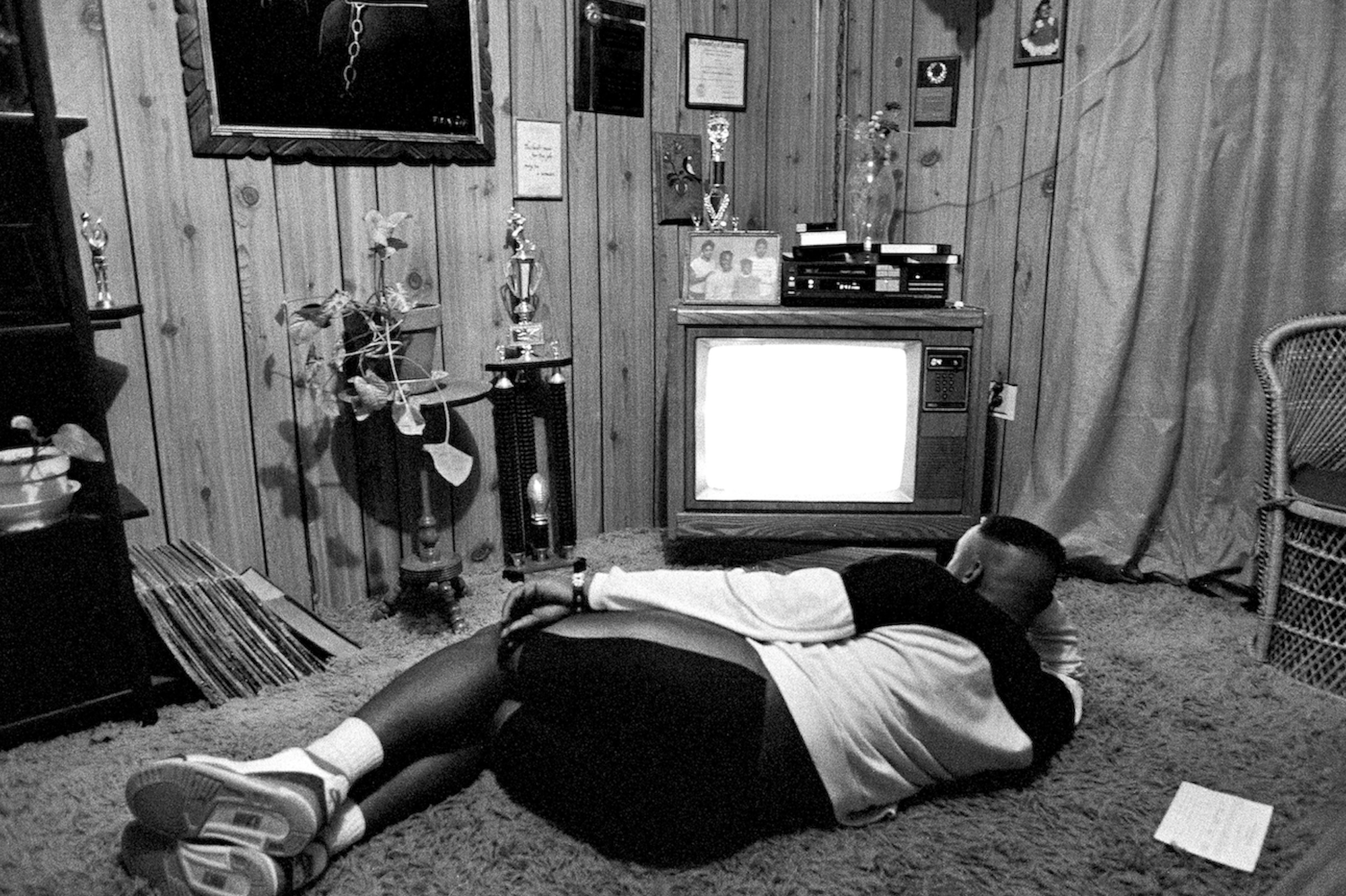 Young man lies on his side on the rug and watches TV with trophies, LP records, and family photos visible