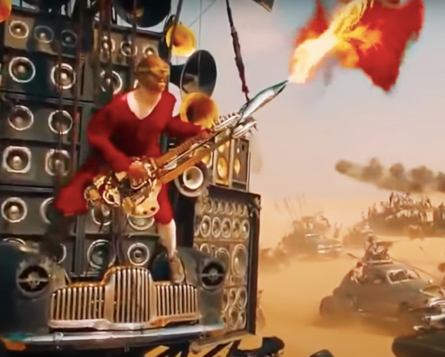the Doof warrior blasts fire from his guitar as he balances on the front of the Doof machine