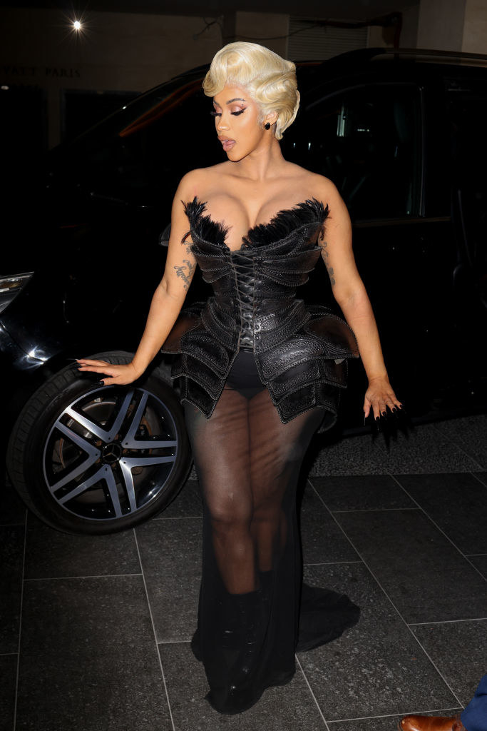 Cardi is wearing a leather topped gown with a see-through skirt and boots