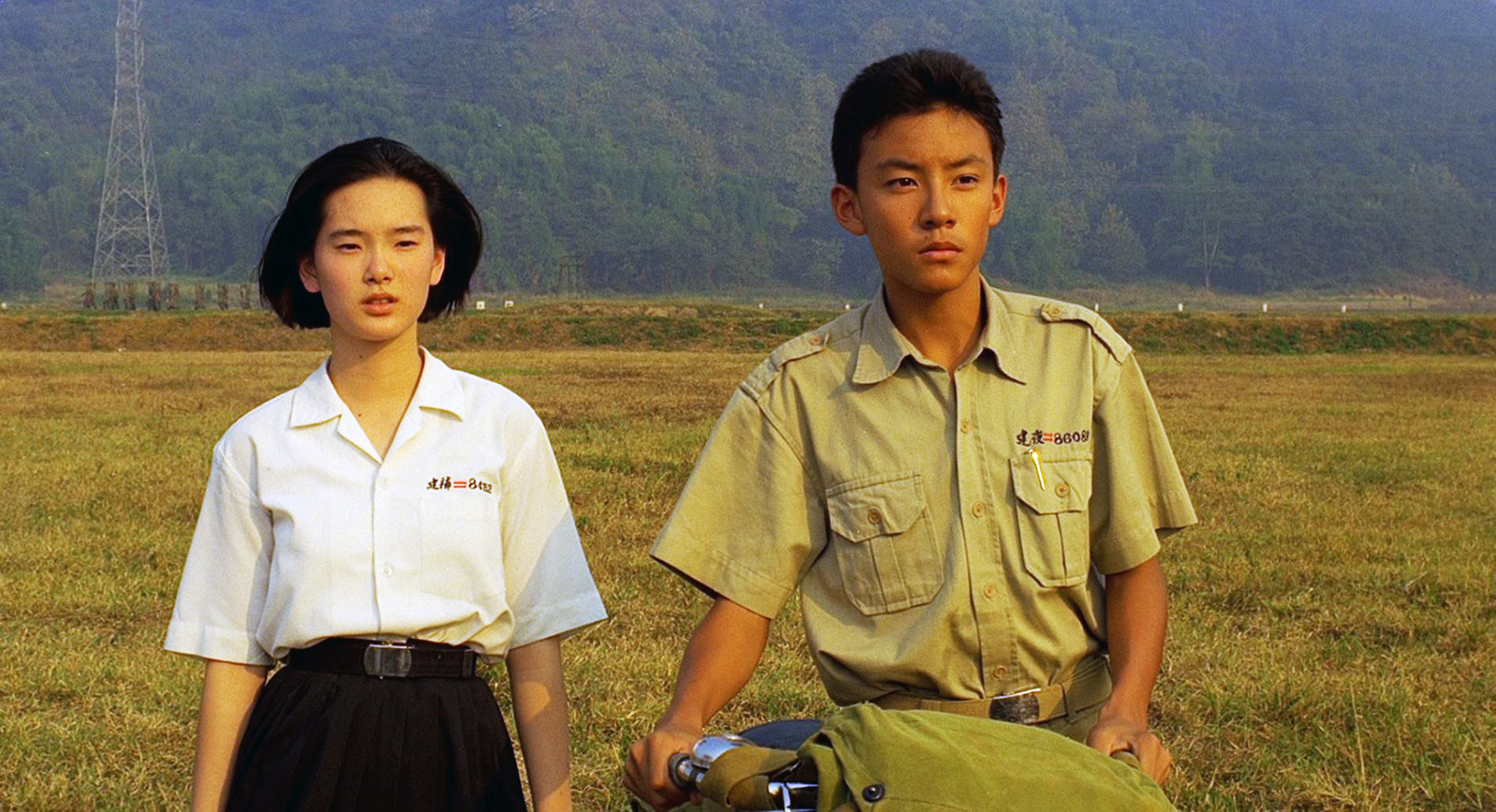 """Chang stands next to Lisa Yang in a field in a still from """"A Brighter Summer Day"""""""